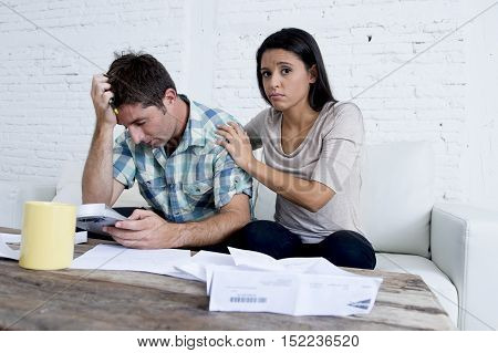 young sad couple at home living room couch calculating monthly expenses worried in stress with bank papers and documents in paying taxes mortage debt and cost of living concept