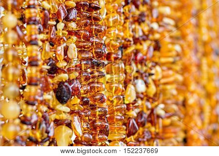 Amber necklace background. Amber necklaces hanging at a street market