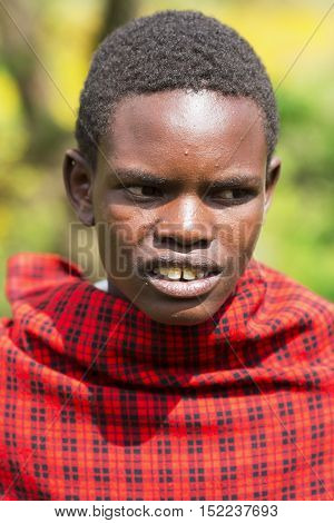AFRICA, KENYA, MAY, 08, 2016 - Maasai Mara tribe men in a red cape at Maasai Mara National Park, Kenya, Africa.  The Maasai (sometimes spelled Masai) are a Nilotic ethnic group of semi-nomadic people inhabiting southern Kenya and northern Tanzania.