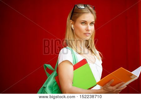 Young girl with open book in headphones on empty Brown background