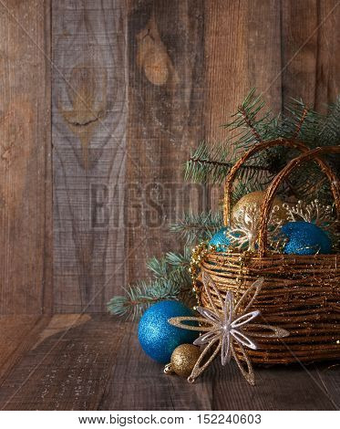 Basket with Christmas decoration on  old wooden plank.