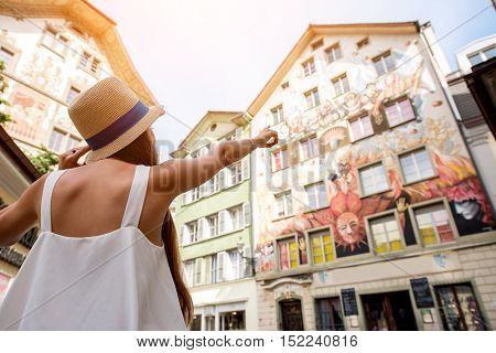 Young female traveler looking on the beautiful ancient buildings in the old town of Lucern city in Switzerland