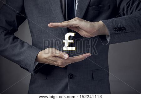 3D Uk Pound Sterling Currency Sign In Between Two Hands Of Businessman.