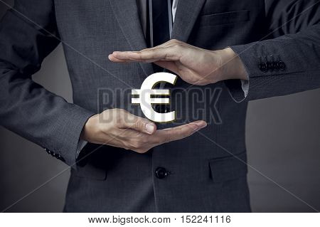 3D Euro currency sign in between two hands of businessman
