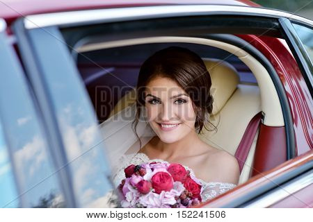 Beauty bride in bridal gown with bouquet and lace veil in the car. Beautiful model girl in a white wedding dress. Female portrait in the auto. Woman with hairstyle. Cute lady outdoors