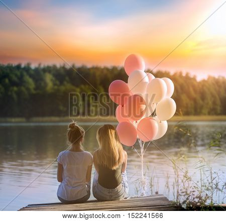Two Friends (girls) Sitting On Jetty At Lake Shore