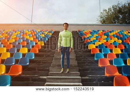Attractive sporty young man model in green shirt standing after training staring at field. Perspective view on stadium chairs.
