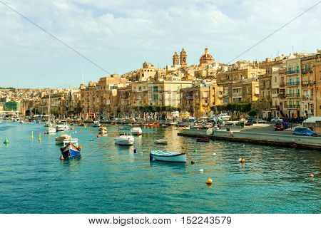 colorful boats in Valletta harbour with view of embankment and cityscape on the background, Malta