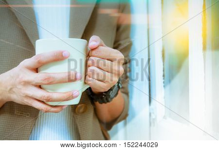 Business woman drinking coffee near window in the room,business content,business background.