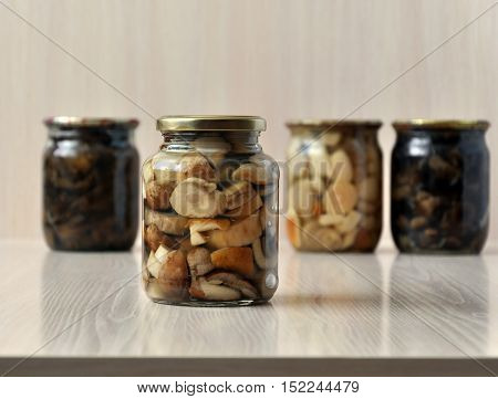 Glass jars with marinated mushrooms on a light wooden background. Close-up.