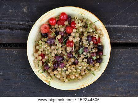 Fresh berries: white currant raspberry gooseberry cherry in a round ceramic plate on dark wooden surface. Top view close up.