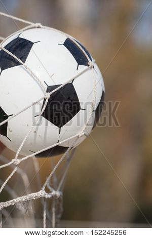 Football or soccer ball in goal net