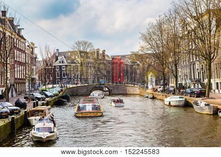 Amsterdam, Netherlands - April 2, 2016: Traditional old buildings, canal and boats with tourists in Amsterdam, Netherlands