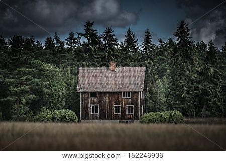 Old house on the swedish countryside abandoned by its owner. Standing all alone at the end of the field.
