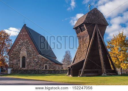 Very old stone church with seperate bell tower made of wood. Church located in Sweden.