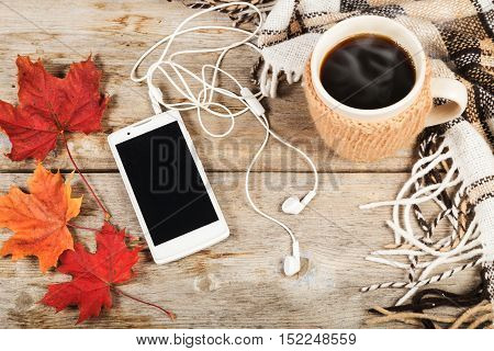 Hot coffee in a large cup, white mobile phone with headphones, three maple leaf, checkered plaid on a wooden table surface