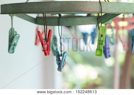 Clothes pegs or clothespins hang on a cord. Plastic clothes pegs on a washing line.(selective focus)