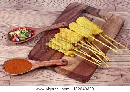 Charcoal boiled pork satay on butcher served , home made in big size, served with Thai cucumber chili sauce as