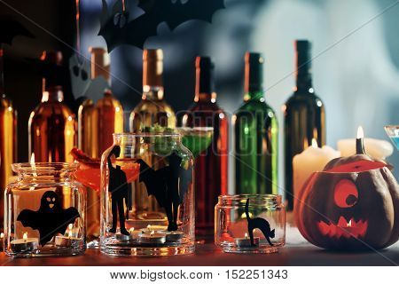 Glass jars with candles and decor for Halloween party