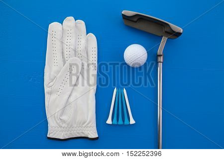 Different golf equipments on the blue desk - flat lay photography