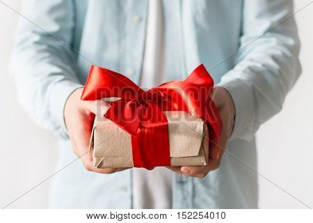 Man's hands with present with craft paper box and red ribbon