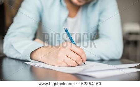 Man writing at the desk. Hands with piece of paper or document and pen. Signing the contract