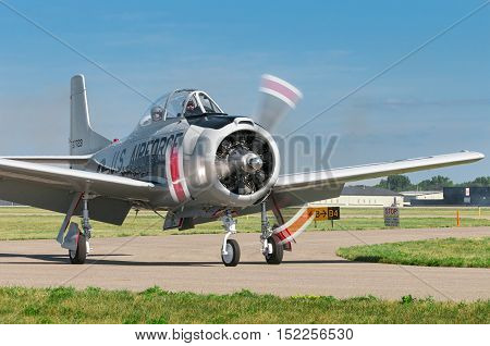 EDEN PRAIRIE MN - JULY 16 2016: AT-6 Texan airplane powers down engine after landing landing at air show. The AT-6 Texan was primarily used as trainer aircraft during and after World War II.