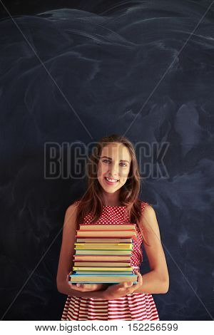 Portrait of beautiful smiling teenage girl in dress standing against blackboard and holding a pile of colorful books