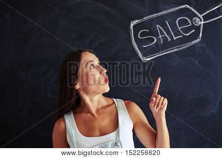 Portrait of young stylish woman with inspired expression on her face in casual clothes pointing at the sale label drawn on blackboard
