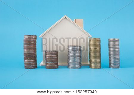 Stack of coins and wooden house symbol on blue soft background
