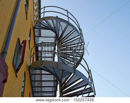Metal modern spiral staircase by an old building