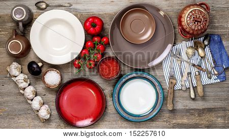 table setting with old antique dishes and vegetables on old wooden table, top view