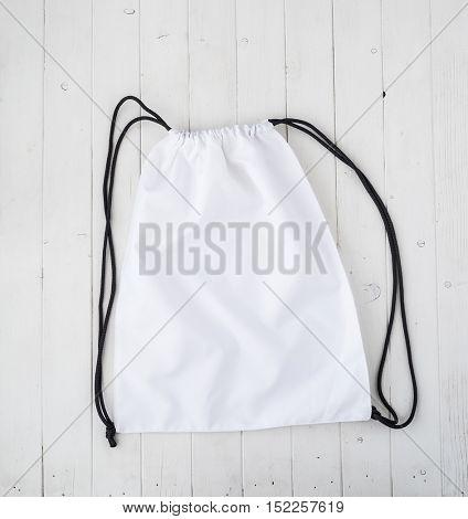 white backpack with black string on planked surface