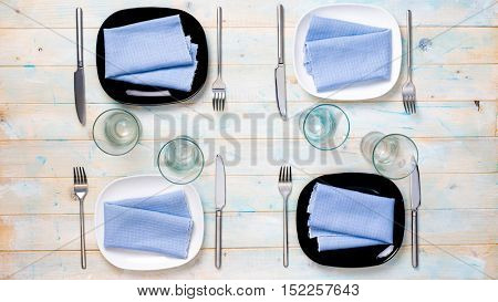 modern table setting with black and white plates, glasses and silverware, top view