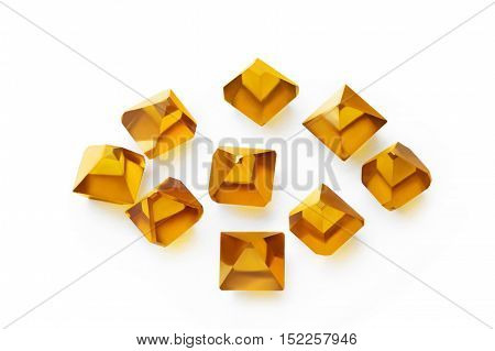 the scattered yellow Monocrystal synthetic diamonds on a white background