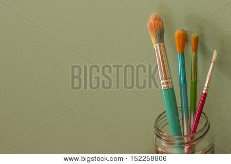 Four colorful artists paintbrushes against a light green background