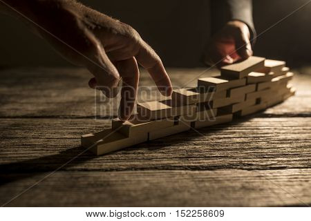Pair of fingers walking up wooden blocks for concept about overcoming difficulty and achieving goals.