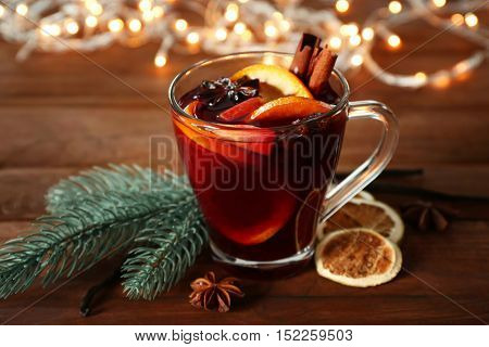 Glass cup of delicious Christmas mulled wine on wooden background, closeup