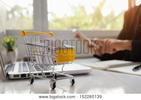 Internet online shopping concept with smartphone and shopping-cart.Vintage tone retro filter effectsoft focus(selective focus)