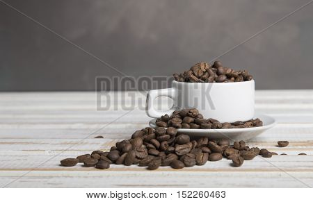 Coffee cup and coffee beans on wooden background. Top view
