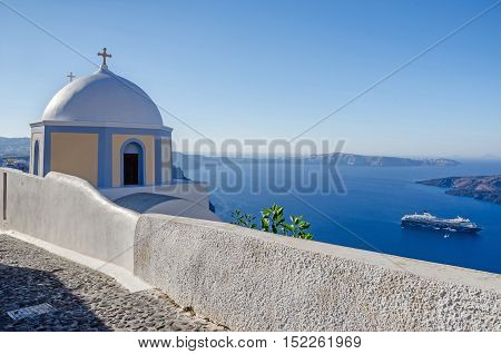 Thira Greece - November 10 2015: One of many typical chapels of Greek Orthodox Church on the greek island Santorini with Aegean Sea cruise liner Mein Schiff 2 and the uninhabited island of Nea Kameni in the background.