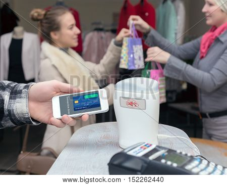 Near Field Communication - Man completing mobile Payment Woman shopping, male Hand holding cell Phone making instant Transaction at Store checkout Terminal Saleswoman and female Consumer on Background