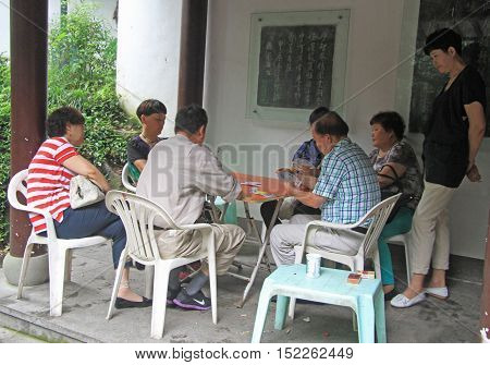People Are Playing Cards Outdoor In Hangzhou, China