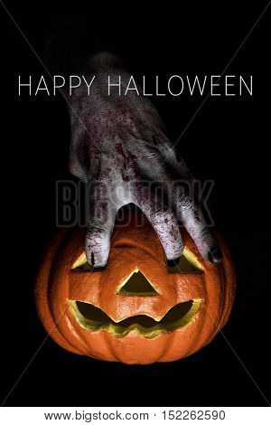 closeup of the scary hand of an undead man putting his fingers in the holes of a carved pumpkin and the text Happy Halloween