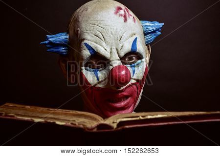 closeup of a scary evil clown reading an old book, against a dark background
