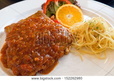 Pork chop. Grilled pork steak in white dish serve with spaghetti vegetable salad and orange.