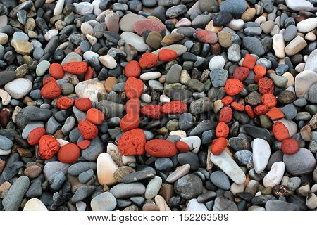 the word sea of red stones on a pebble beach