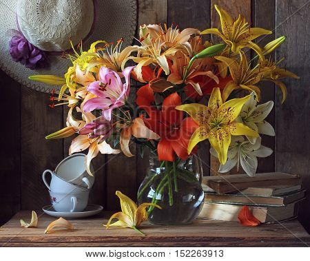 Still-life with a bouquet of lilies in a glass jar summer hats books and cups.