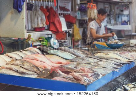 Singapore, Republic of Singapore - May 5, 2016: asian man selling fresh fish at traditional market stall