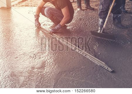 Man Plasterer Screed Concrete On Cement  For Floor In Building Construction With Vintage Toned.